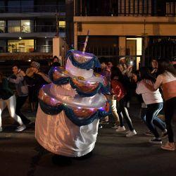 Familiares y amigos bailan alrededor de un pastel humano dado a un joven de 15 años para su cumpleaños en Montevideo en medio de la pandemia de COVID-19. - Debido a las restricciones pandémicas, un uruguayo convirtió su empresa de publicidad en un negocio de cumpleaños en cuarentena, con un pastel humano gigante y altavoces para celebrar. | Foto:Eitan Abramovich / AFP