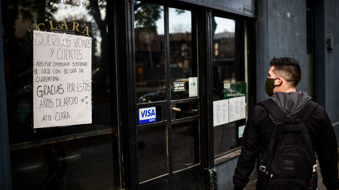"""A man walks past a closed restaurant with a sign reading """"Dear neighbours and clients, it was impossible for us to sustain the place with 80 days of quarantine. Thank you for these years' support"""" in Buenos Aires, on June 17, 2020, amid the new coronavirus pandemic."""