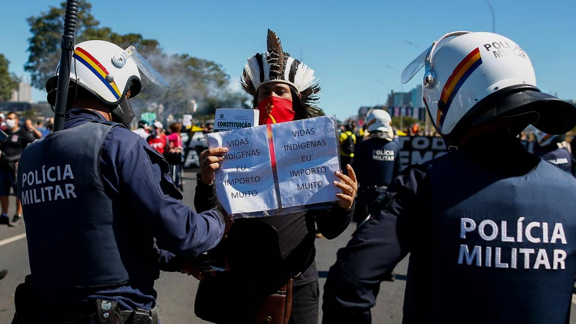 An indigenous protester is approached by militarised policemen during a protest against Brazilian President Jair Bolsonaro and racism in Brasilia, Brazil, on June 21, 2020, amid the Covid-19 coronavirus pandemic.
