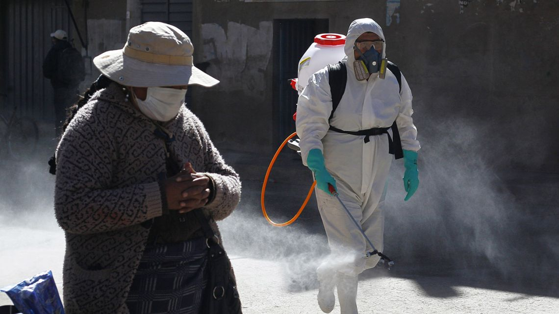 A municipal worker sprays disinfectant past a street vendor at a market in Puno, Peru, near the border with Bolivia, on June 10, 2020.