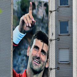 Una cartelera que representa al tenista serbio Novak Djokovic y el monasterio cristiano ortodoxo de Ostrog se ve en un edificio en Belgrado. - Novak Djokovic también dio positivo por coronavirus. | Foto:ANDREJ ISAKOVIC / AFP