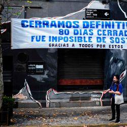 Un hombre afuera de una barra de cerveza cerrada debajo de una pancarta que dice  | Foto:RONALDO SCHEMIDT / AFP