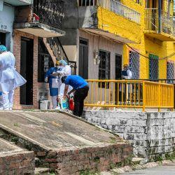 Los trabajadores de la salud son fotografiados durante una prueba aleatoria en el vecindario de Santa Cruz en Medellín, Colombia, durante la pandemia de coronavirus Covid-19. | Foto:JOAQUIN SARMIENTO / AFP