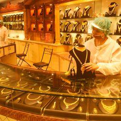 Un empleado que usa un equipo de protección organiza joyas de oro dentro de una sala de exposición después de que el gobierno alivió un bloqueo nacional impuesto como medida preventiva contra el coronavirus COVID-19, en Calcuta. | Foto:Dibyangshu Sakar / AFP