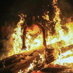 Un joven salta sobre el fuego mientras la gente participa en una celebración tradicional de la noche del solsticio de mediados de verano (Festival Rasos) en el Museo al aire libre de Lituania en Rumsiskes. | Foto:PETRAS MALUKAS / AFP