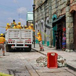 Los trabajadores retiran los escombros y colocan cintas de seguridad alertando sobre un edificio dañado después de un terremoto en Oaxaca, México. | Foto:PATRICIA CASTELLANOS / AFP