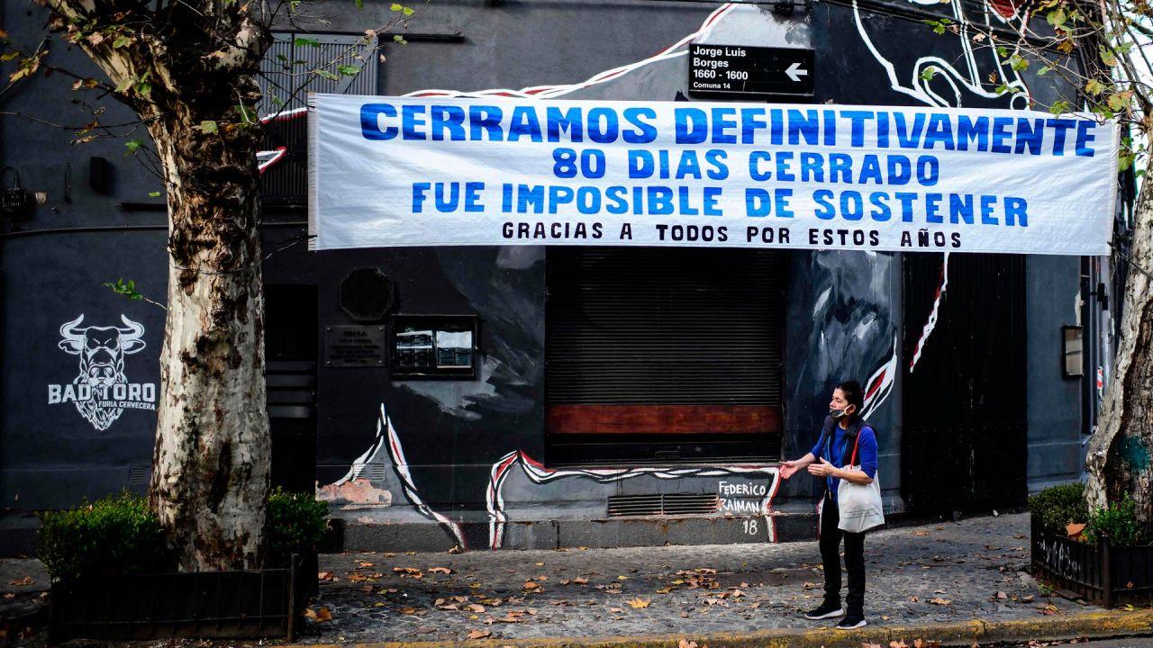Un hombre afuera de una barra de cerveza cerrada debajo de una pancarta que dice    Foto:RONALDO SCHEMIDT / AFP