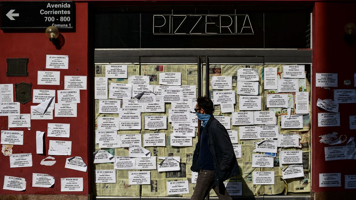 A man walks in front of a closed pizza restaurant that's covered with papers of claims from former employees, in Buenos Aires, on June 17, 2020.