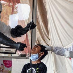Los medicos toman una muestra de hisopo nasal de un niño en un centro de detección del coronavirus COVID-19, en Hyderabad.   Foto:STR / AFP