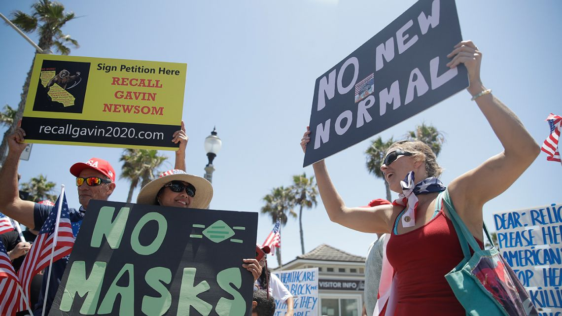 Demonstrators hold signs as they protest the lockdown and wearing masks Saturday, June 27, 2020, in Huntington Beach, California.