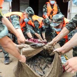 Los policías paramilitares de China ayudan a las personas afectadas por las inundaciones a salvar sus propiedades después de que las fuertes lluvias causaron inundaciones en el condado de Mianning. | Foto:STR / AFP