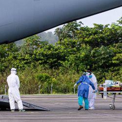 El personal médico lleva a un paciente infectado con el nuevo coronavirus (Covid-19) a un Airbus A400M en la base aérea de Guayana 367 en Matoury, cerca de Cayenne, en el departamento francés de ultramar de Guayana. | Foto:Jody Amiet / AFP