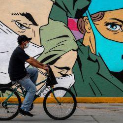 Un hombre viaja en bicicleta frente a un mural relacionado con el coronavirus de los artistas urbanos Mick Martínez y  | Foto:HERIKA MARTINEZ / AFP