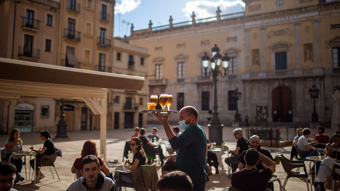 In this Monday, May 11, 2020 file photo, a waiter carries beers for customers sitting at a terrace bar in Tarragona, Spain. The European Union announced Tuesday, June 30, 2020 that it will reopen its borders to travelers from 14 countries, but most Americans have been refused entry for at least another two weeks due to soaring coronavirus infections in the United States.
