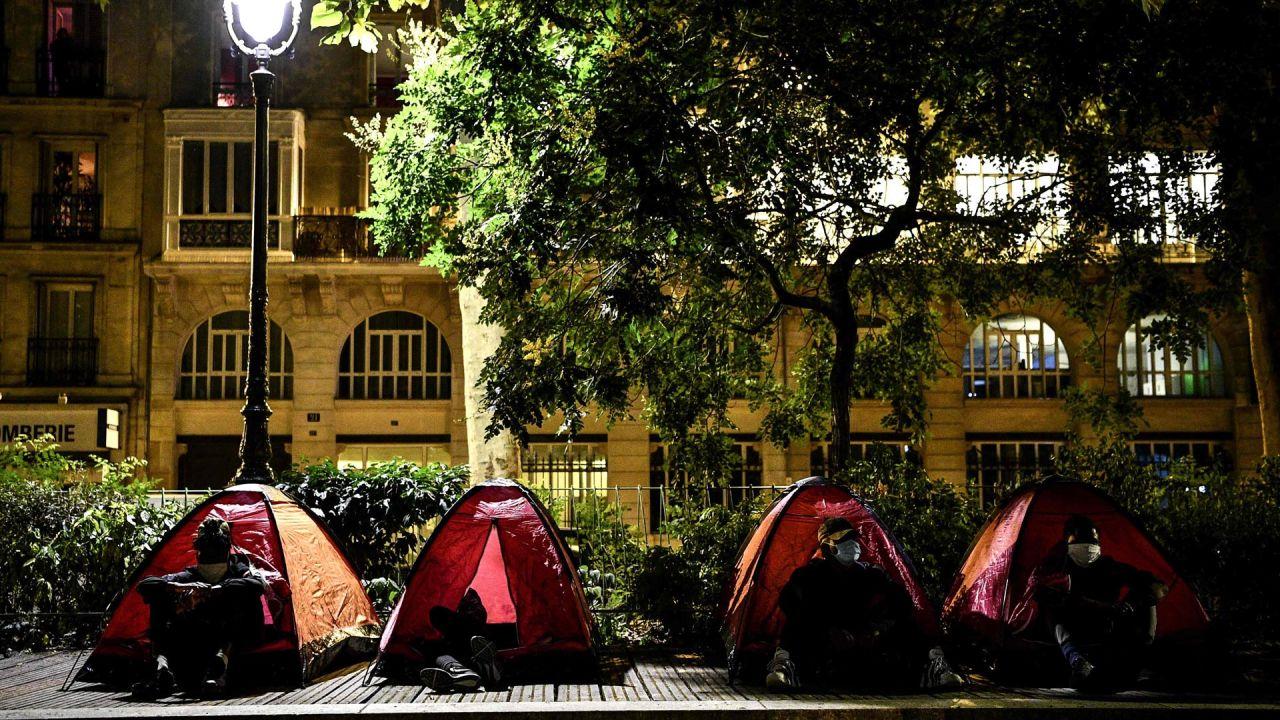 Jóvenes migrantes se sientan en tiendas de campaña en un campamento improvisado organizado por voluntarios de organizaciones benéficas Médicos Sin Fronteras en un parque público en París.   Foto:Christophe Archanbault / AFP