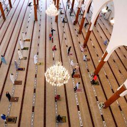 Los fieles que se mantienen a una distancia segura el uno del otro realizan oraciones en una mezquita en el emirato de Sharjah después de que los Emiratos Árabes Unidos reabran los lugares de culto después de meses de cierre para evitar la propagación del coronavirus Covid-19. | Foto:KARIM SAHIB / AFP