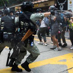 La policía antidisturbios despliega gas pimienta contra periodistas mientras los manifestantes se reunían para una manifestación contra una nueva ley de seguridad nacional en Hong Kong.   Foto:DALE DE LA REY / AFP