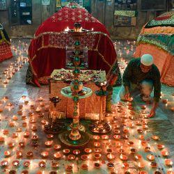 Un devoto musulmán enciende lámparas de aceite en el antiguo Mausoleo del Sultán Ahmed Shah, fundador de la ciudad de Ahmedabad, antes de ofrecer oraciones por el bienestar de todos los ciudadanos de Ahmedabad contra la propagación del coronavirus COVID-19, en Ahmedabad.   Foto:SAM PANTHAKY / AFP
