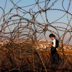 Una mujer judía vestida con una máscara se ve a través de alambre de espino mientras reza mientras los colonos israelíes se reúnen en una colina al lado de la ciudad palestina de Halhul, al norte de Hebrón, en la Cisjordania ocupada.   Foto:MENAHEM KAHANA / AFP