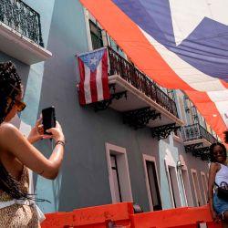 Un turista toma fotos de una pareja frente a la mansión del gobernador en San Juan, Puerto Rico, durante la pandemia de coronavirus.    Foto:Ricardo Arduengo / AFP