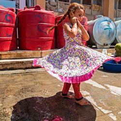 Una niña pasa junto a mujeres que lavan ollas y sartenes junto a cisternas en el patio de un edificio escolar donde los sirios, desplazados del área de Ras al-Ain por la ofensiva turca en el noreste, se alojan en la ciudad de Hasakah.   Foto:Delil Souleiman / AFP