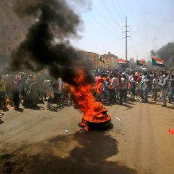 Manifestantes sudaneses quemaron neumáticos durante una protesta en la calle Sixty en el este de la capital, Jartum - Decenas de miles de sudaneses salieron a las calles en varias ciudades y en la capital pidiendo reformas y exigiendo justicia para los asesinados en manifestaciones antigubernamentales que derrocaron al presidente Omar al-Bashir el año pasado.    Foto:ASHRAF SHAZLY / AFP