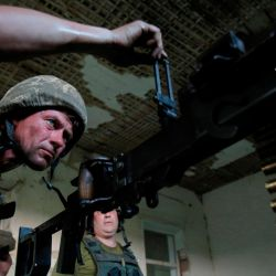 Un militar ucraniano prepara una ametralladora para un combate en una posición en primera línea con separatistas respaldados por Rusia en la aldea de Krymske, región de Lugansk. | Foto:Anatolii Stepanov / AFP