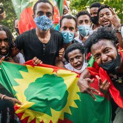 Los manifestantes se regocijan cuando los miembros de la comunidad Oromo cierran el carril hacia el oeste de la carretera interestatal 94, cerca de Lexington Ave, durante una protesta después de la muerte del músico y activista Hachalu Hundessa en St Paul, Minnesota.  | Foto:Brandon Bell / Getty Images / AFP