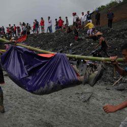 Los rescatistas recuperan cuerpos cerca del área de deslizamiento de tierra en el sitio de minería de jade en Hpakhant en el estado de Kachin. | Foto:Zaw Moe Htet / AFP