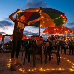 Un joven palestino prepara mesas para clientes en una cafetería de playa en la ciudad de Gaza. | Foto:MOHAMMED ABED / AFP