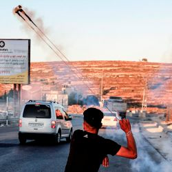 Un manifestante palestino usa un tirachinas para arrojar botes de gas lacrimógeno a las fuerzas de seguridad israelíes durante los enfrentamientos tras una manifestación contra el plan de Israel de anexar partes de la Cisjordania ocupada, en la entrada norte de la ciudad cisjordana de Ramallah, cerca del asentamiento judío de Beit.  | Foto:ABBAS MOMANI / AFP