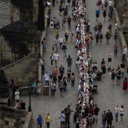 La gente pasa y se sienta en una mesa de medio kilómetro de largo colocada en el Puente de Carlos en Praga para celebrar el final de las restricciones vinculadas a la nueva pandemia de coronavirus. - Se proponen unos 2.000 asientos con personas invitadas a traer y compartir comida. | Foto:Michal Cizek / AFP