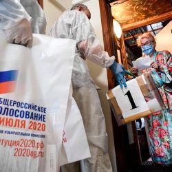 Una mujer se para junto a la puerta de su piso mientras se prepara para emitir su voto en una urna móvil durante una votación nacional sobre reformas constitucionales en Moscú. | Foto:Alexander Nemenov / AFP
