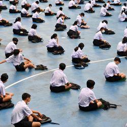 Los estudiantes asisten a la ceremonia de izamiento de la bandera en una escuela secundaria en Bangkok, ya que las escuelas reabrieron sus puertas después de ser cerradas temporalmente debido a la amenaza del nuevo coronavirus COVID-19. | Foto:ROMEO GACAD / AFP