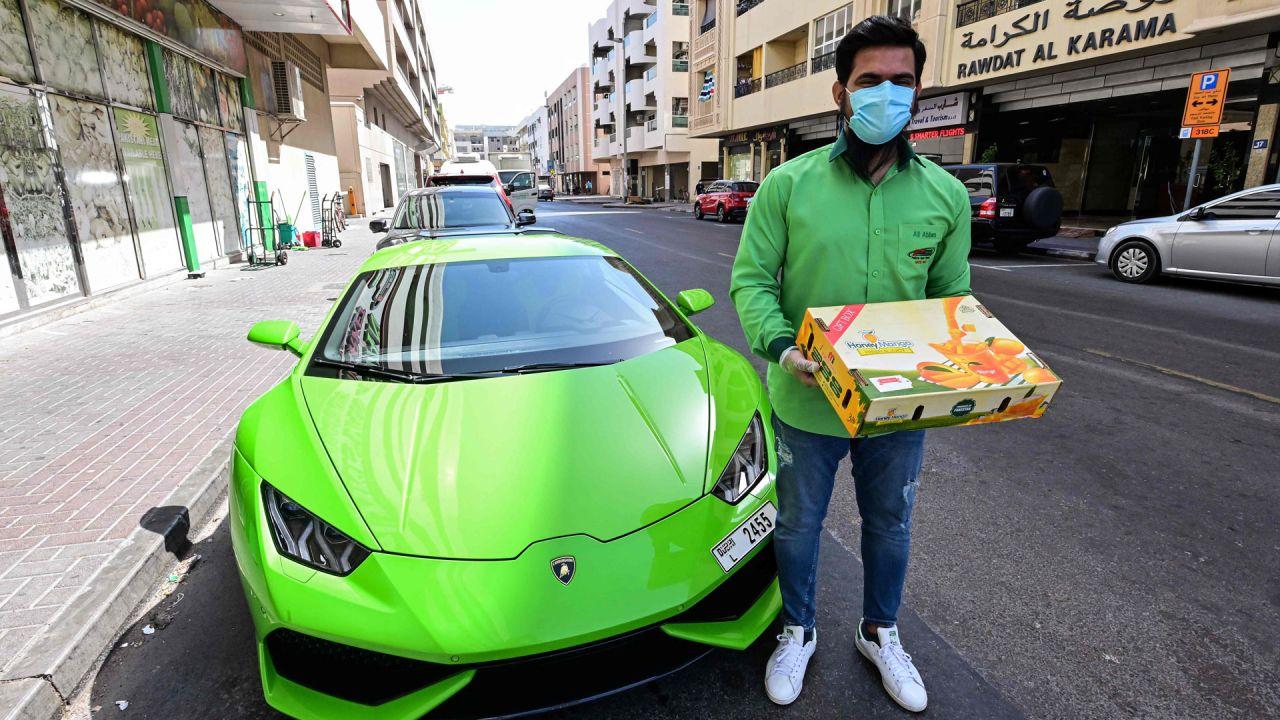 Hanzeb Yaseen, director gerente de Pakistan Super Market Dubai, se encuentra fuera del edificio del supermercado junto a un automóvil deportivo Lamborghini Huracán antes de entregar una orden de mangos, en el emirato del Golfo. | Foto:GIUSEPPE CACACE / AFP