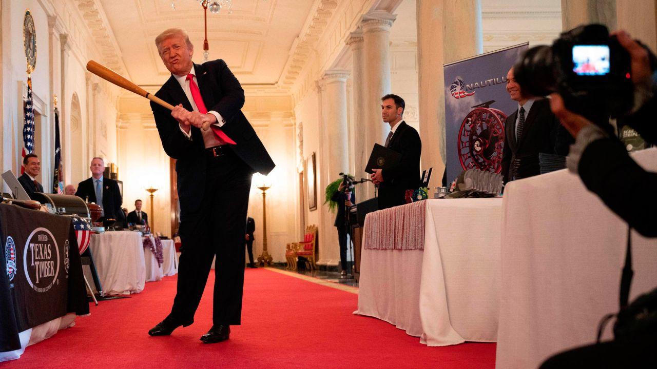El presidente de los Estados Unidos, Donald Trump, se balancea con un bate de Texas Timber antes de hablar en un evento de exhibición del Spirit of America para destacar a las pequeñas empresas en el gran vestíbulo de la Casa Blanca, en Washington, DC. | Foto:JIM WATSON / AFP