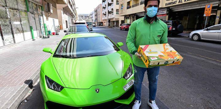 Hanzeb Yaseen, director gerente de Pakistan Super Market Dubai, se encuentra fuera del edificio del supermercado junto a un automóvil deportivo Lamborghini Huracán antes de entregar una orden de mangos, en el emirato del Golfo.