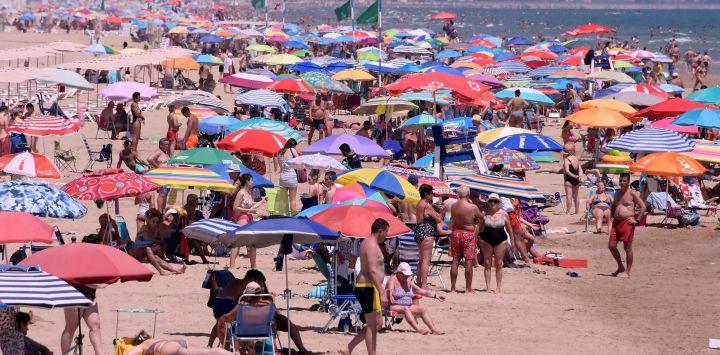 La gente disfruta de un día en Nord Beach en Gandia, cerca de Valencia. - La Unión Europea reabrió sus fronteras a los visitantes de 15 países, pero excluyó a los Estados Unidos, donde las muertes por coronavirus están aumentando una vez más, seis meses después del primer clúster se informó en China.