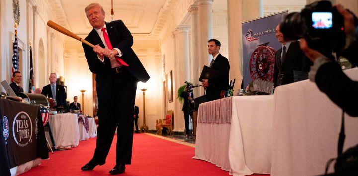 El presidente de los Estados Unidos, Donald Trump, se balancea con un bate de Texas Timber antes de hablar en un evento de exhibición del Spirit of America para destacar a las pequeñas empresas en el gran vestíbulo de la Casa Blanca, en Washington, DC.