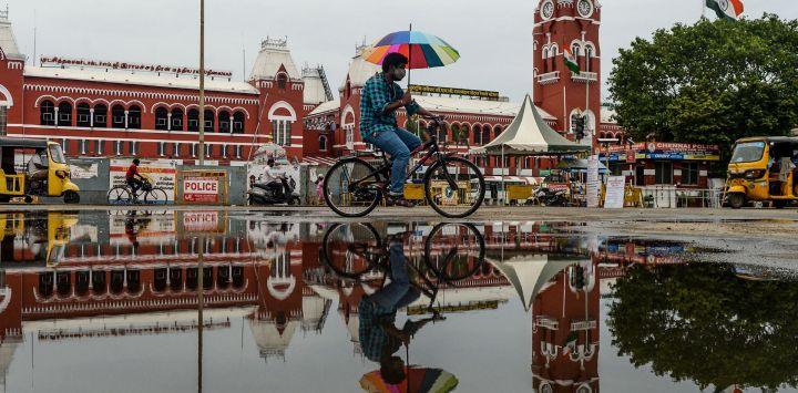 Un ciclista con un paraguas circula junto a un charco de agua después de la lluvia en Chennai.