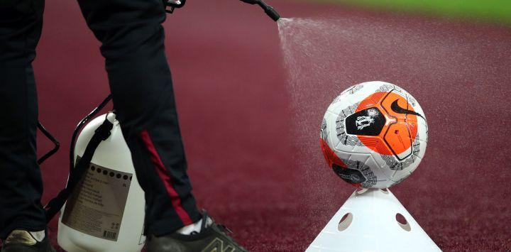 Una pelota de partido se rocía con desinfectante durante el partido de fútbol de la Premier League inglesa entre West Ham United y Chelsea en el London Stadium, en el este de Londres.