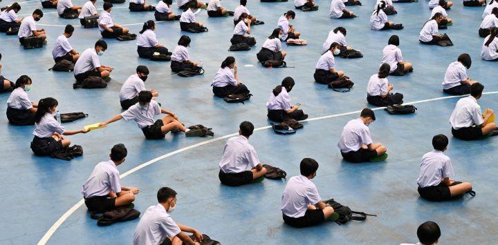 Los estudiantes asisten a la ceremonia de izamiento de la bandera en una escuela secundaria en Bangkok, ya que las escuelas reabrieron sus puertas después de ser cerradas temporalmente debido a la amenaza del nuevo coronavirus COVID-19.
