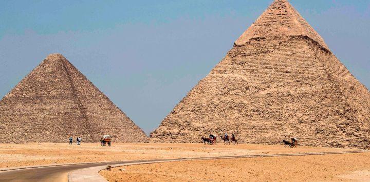 Esta imagen muestra una vista de guías de camellos esperando cerca de la Gran Pirámide (de izquierda a derecha) de Khufu (Keops) y la Pirámide de Khafre (Chephren) en la necrópolis de las pirámides de Giza en las afueras del suroeste de la capital egipcia El Cairo , a medida que el sitio arqueológico reabre mientras el país alivia las restricciones establecidas debido a la pandemia de coronavirus COVID-19.