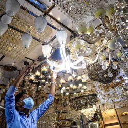Un comerciante limpia el polvo de un candelabro en una tienda de luces en Dhaka. | Foto:Munir Uz zaman / AFP