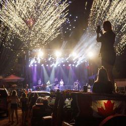 La gente toma fotos y mira cómo los fuegos artificiales explotan detrás del escenario de un concierto de Dean Brody para celebrar el Día de Canadá en Markham, Canadá. | Foto:Cole Burston / Getty Images / AFP