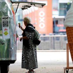 Una mujer compra un helado en Gabriel's Wharf junto al río Támesis en Londres. El gobierno ha estado suavizando las órdenes de quedarse en casa impuestas a fines de marzo con la reapertura de bares, restaurantes y museos este fin de semana. | Foto:Tolga Akmen / AFP