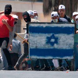 Los manifestantes palestinos, de pie detrás de un escudo pintado con los colores de la bandera israelí, arrojan piedras hacia las tropas israelíes (sin ser vistas) durante una manifestación en la aldea de Kfar Qaddum en Cisjordania. | Foto:JAAFAR ASHTIYEH / AFP