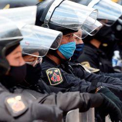 La policía antidisturbios espera mientras el personal médico de diferentes instituciones protesta contra el reciclaje de máscaras faciales en medio de la pandemia de coronavirus COVID-19 a lo largo de la Avenida Reforma en la Ciudad de México. | Foto:ALFREDO ESTRELLA / AFP