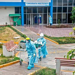 Las enfermeras transfieren a un paciente COVID-19 a la Unidad de Cuidados Intensivos del Hospital Alberto Sabogal Sologuren, en Lima, en medio de la nueva pandemia de coronavirus. | Foto:ERNESTO BENAVIDES / AFP