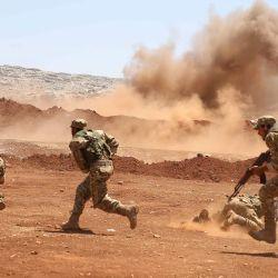 Miembros del Frente de Liberación Nacional de la oposición siria participan en un entrenamiento militar en el campo norte de la provincia de Idlib. | Foto:AAREF WATAD / AFP